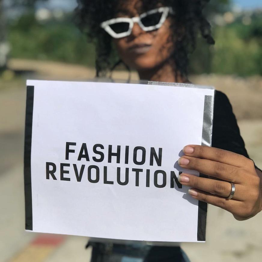 Mulher segurando placa com a mensagem Fashion Revolution