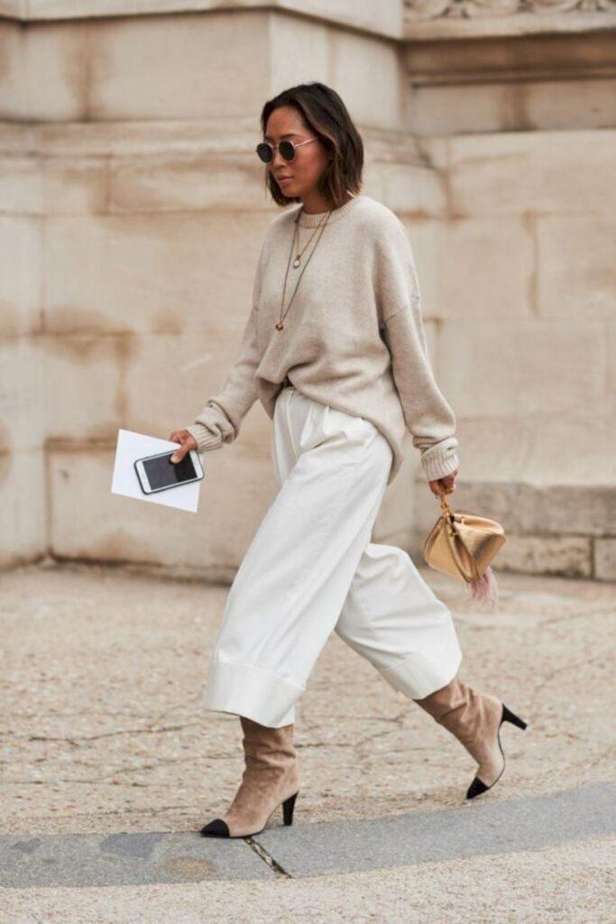 Mulher veste pantacourt branca com trico bege, óculos de sol, bota cano longo e finaliza com a bolsa clutch doura